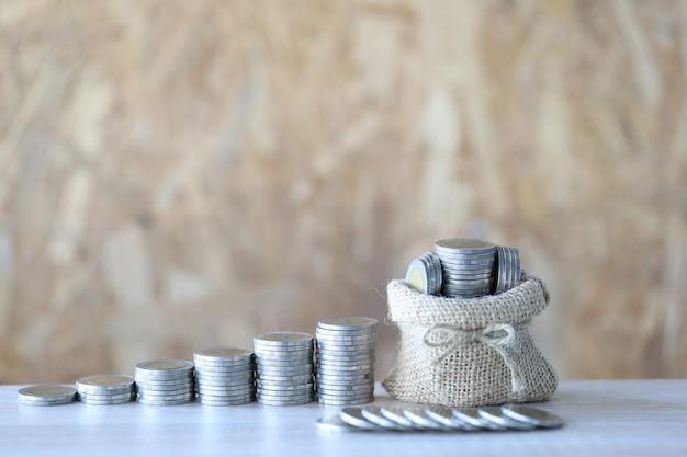 Borsa dei soldi con la pila di soldi delle monete su fondo più legnoso