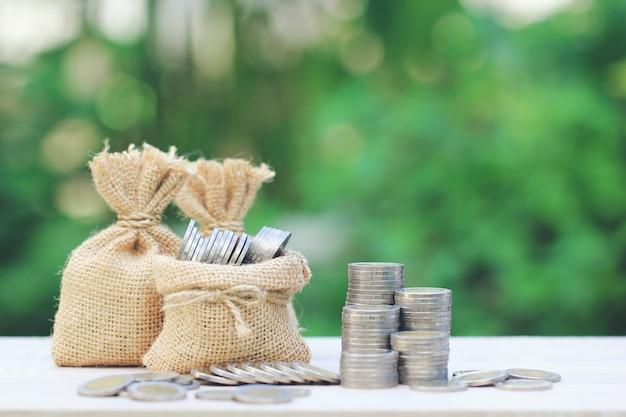 Borsa dei soldi con la pila di soldi delle monete su fondo verde naturale