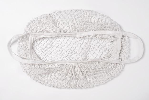 Borsa di corda riutilizzabile vuota di acquisto del cotone su fondo bianco. borsa o shopper in rete ecologica. rifiuto della plastica, zero sprechi, concetto di riciclaggio e riutilizzo.