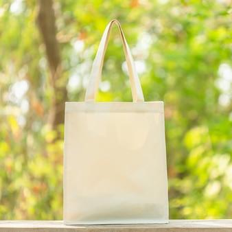 Borsa di cotone bianco messo sul tavolo di legno con spazio per il testo o la pubblicità. il sacchetto di cotone può essere utilizzato per lo shopping per sostituire il sacchetto di plastica sulla natura verde