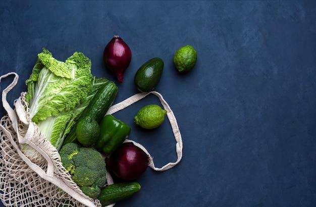 Borsa di drogheria verde e viola fresca in un fondo blu scuro