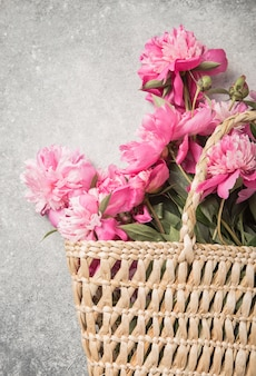 Borsa di paglia con fiori di peonia rosa su sfondo grigio.