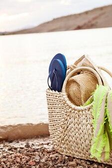 Borsa di paglia estiva e accessori da spiaggia sulla riva