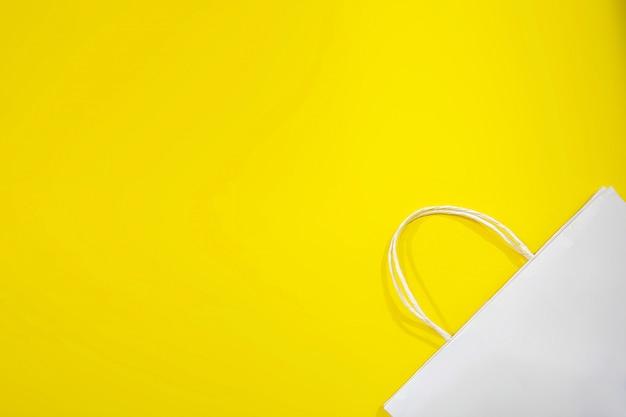 Borsa di tela o borse di carta e cose fatte con materiali naturali con sfondo giallo.