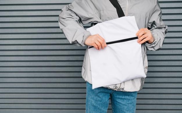 Borsa eco bianca nelle mani di un giovane uomo elegante su una parete grigia, con la mano apre la chiusura a cerniera in eco bag. riutilizzabile elegante shopping bag nelle mani di un uomo