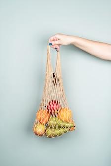 Borsa eco con frutta in mano di una donna su un muro grigio. zero sprechi. dieta sana.