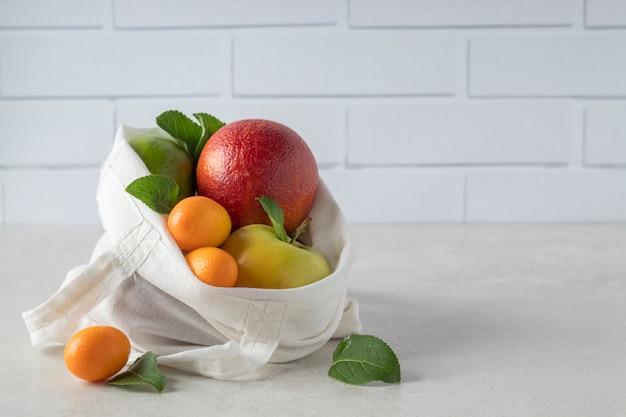 Borsa ecologica con diversi frutti tropicali sul tavolo, copia del testo dello spazio. shopping rispettoso dell'ambiente