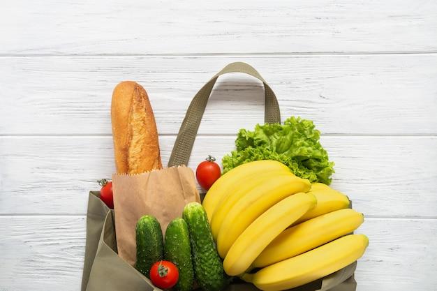 Borsa ecologica verde dal supermercato con prodotti: pane, insalata, pomodori, banane, cetrioli su bianco
