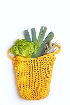 Borsa in cotone a cordoncino con erbe e frutti verdi. immagine verticale. il concetto di conservazione della natura e zero sprechi.