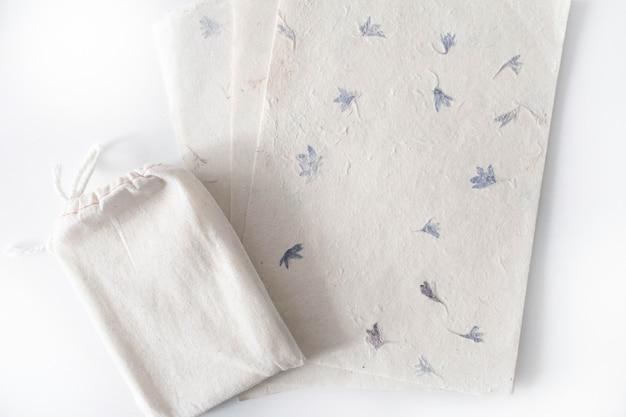 Borsa in cotone con mazzo di tarocchi con fogli di carta ruvida. sacchetto delle carte di tarocchi di boho sulla tavola bianca con copyspace