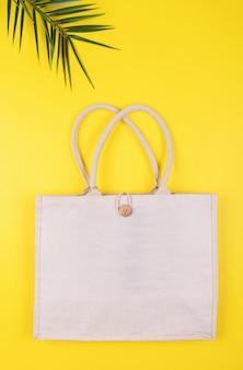 Borsa in cotone ecologico con foglia di palma su un giallo, copyspace, stile minimal natura. riciclaggio di conservazione ambientale