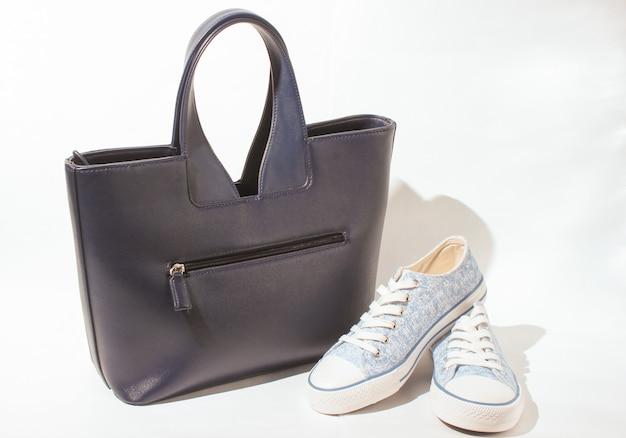 Borsa in pelle alla moda e scarpe da ginnastica sopra bianco