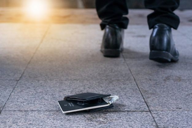 Borsa in pelle con soldi e passaporto distesi sul marciapiede e piedi di un uomo in uscita
