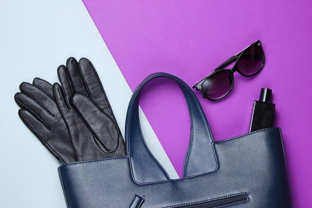 Borsa in pelle, occhiali da sole, guanti, bottiglia di profumo sul tavolo grigio-viola. accessori moda femminile