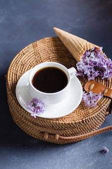 Borsa in rattan alla moda, tazza di caffè e lillà viola nel cono di cialda su priorità bassa concreta blu.