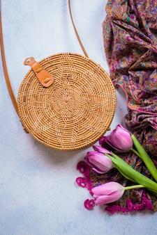 Borsa in rattan alla moda, tulipani e sciarpa su sfondo chiaro. copia spazio, vista dall'alto