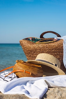 Borsa intrecciata moderna delle donne sulla pavimentazione bianca sulla spiaggia