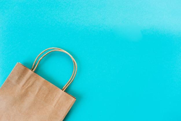 Borsa kraft su sfondo turchese. imballaggio ecologico per lo shopping.