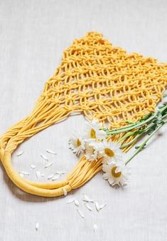 Borsa macramè gialla fatta a mano con bouquet di camomilla sul lino
