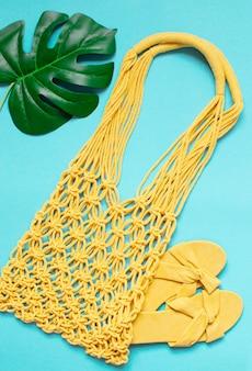 Borsa macramè gialla fatta a mano su azzurro, ecologica. concetto di spiaggia estiva moderna