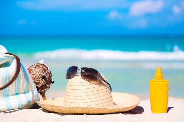 Borsa, maracas, cappello di paglia con occhiali da sole e bottiglia di crema solare sulla sabbia bianca