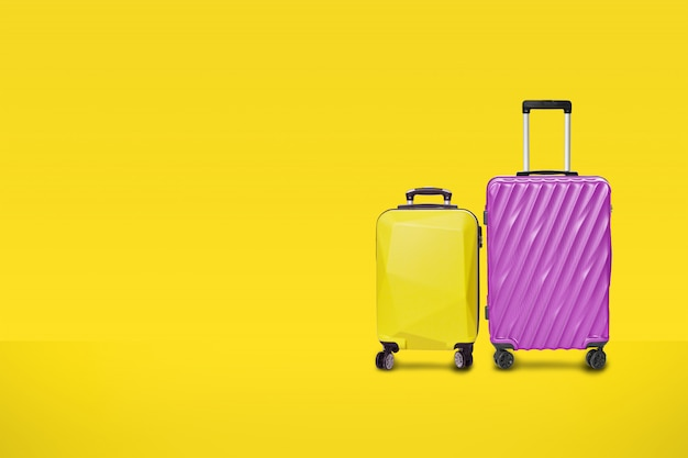 Borsa moderna viola valigie giallo su sfondo giallo.