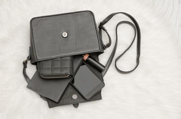 Borsa nera aperta con oggetti caduti, taccuino, cellulare, borsa. la pelliccia bianca su sfondo, vista dall'alto. concetto di moda