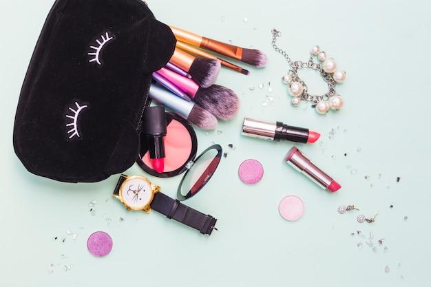 Borsa nera con pennelli per il trucco; braccialetto; orologio da polso e prodotti cosmetici su sfondo pastello