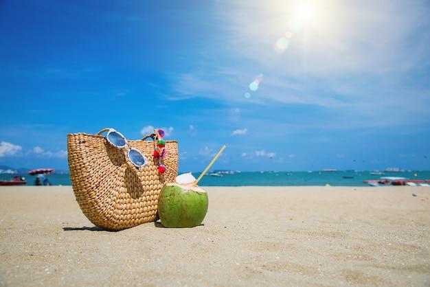 Borsa, occhiali da sole e cocco su una spiaggia tropicale