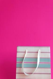 Borsa pacchetto a strisce su sfondo rosa brillante.