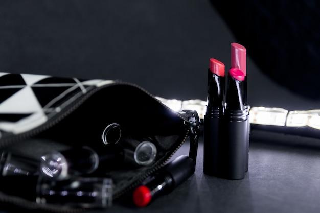 Borsa per il trucco in bianco e nero con set di rossetti.
