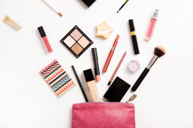 Borsa per il trucco in pelle con prodotti cosmetici di bellezza che si rovesciano sulla superficie bianca