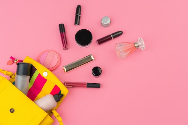Borsa piccola donna piena di prodotti cosmetici su sfondo rosa brillante