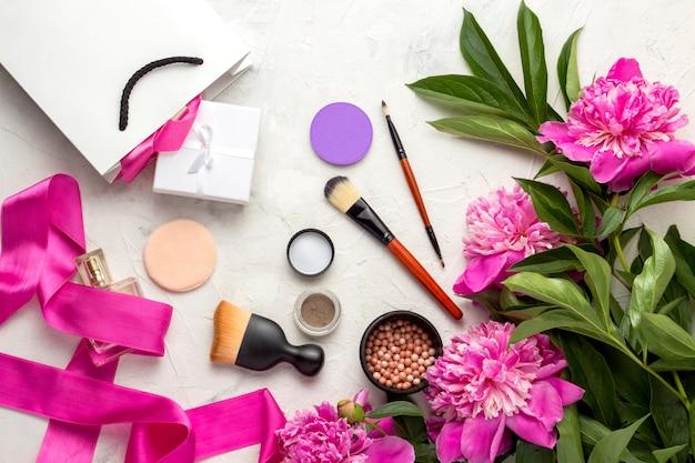 Borsa regalo bianca e confezionata con regalo, fard, sponzhiki, pennello, ombretto, bottiglia di profumo, nastro rosa e peonie rosa. vista dall'alto.