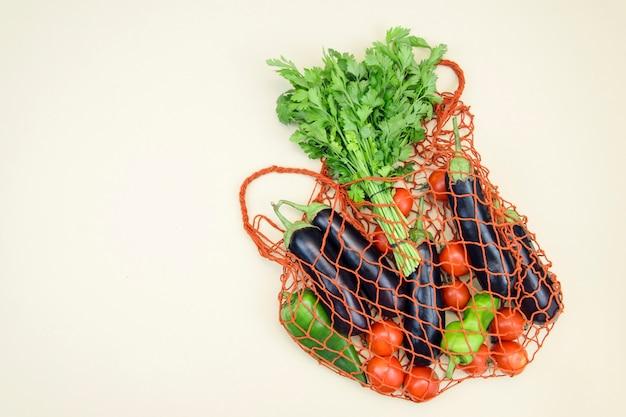 Borsa riutilizzabile della maglia dello shopping con verdure eco. vista dall'alto e copia spazio. zero rifiuti, concetto privo di plastica. cibo rinfrescante estivo, concetto eco-compatibile