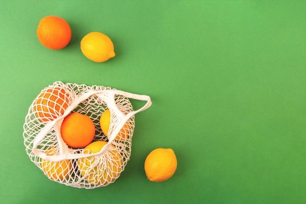 Borsa riutilizzabile della rete della frutta con le arance ed i limoni su fondo verde. concetto di rifiuti zero. disteso, copia spazio.
