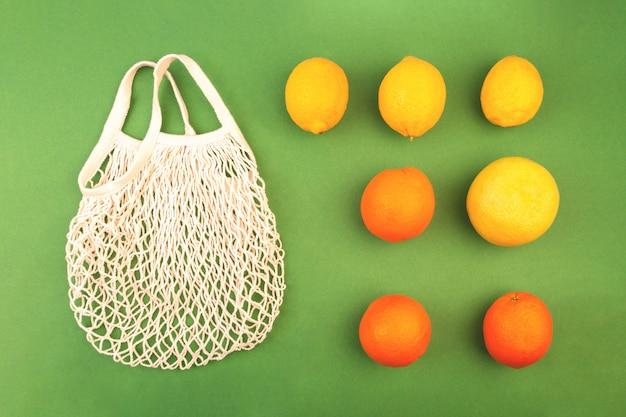 Borsa riutilizzabile della rete della frutta con le arance ed i limoni su fondo verde. concetto di rifiuti zero. disteso.