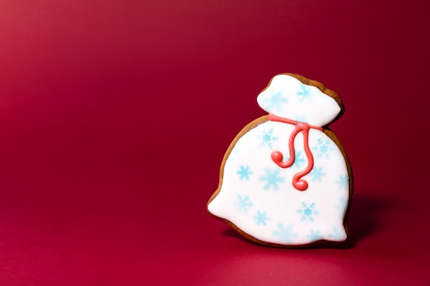 Borsa rossa chiusa del babbo natale del biscotto del pan di zenzero su rosso