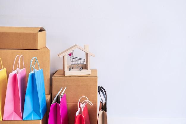 Borsa shopping colorata con pila di scatole di cartone a casa