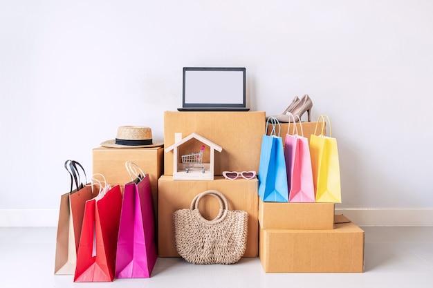 Borsa shopping colorata con una pila di scatole di cartone e articoli di moda a casa
