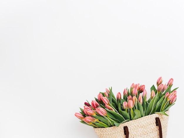 Borsa shopping ecologica tessuta con tulipani di fronte a uno sfondo bianco muro