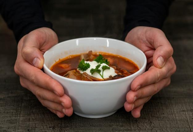 Borsch in un piatto bianco, zuppa di barbabietola con panna acida e prezzemolo