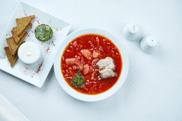 Borsch ucraino delizioso con carne di maiale, lardo, panna acida e pane di segale su bianco.