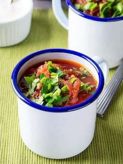 Borscht di zuppa di barbabietola russa in tazze di smalto