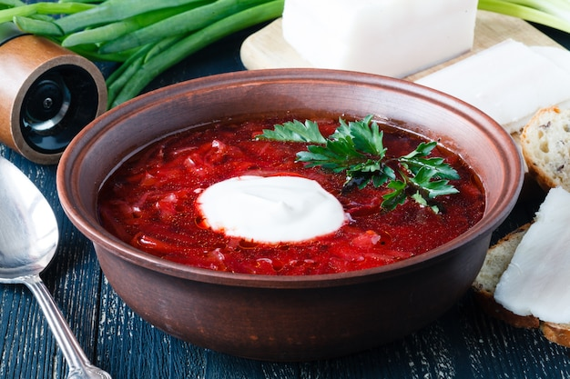 Borscht, zuppa di barbabietola vegetariana ed ingredienti su superficie scura, vista alta vicina