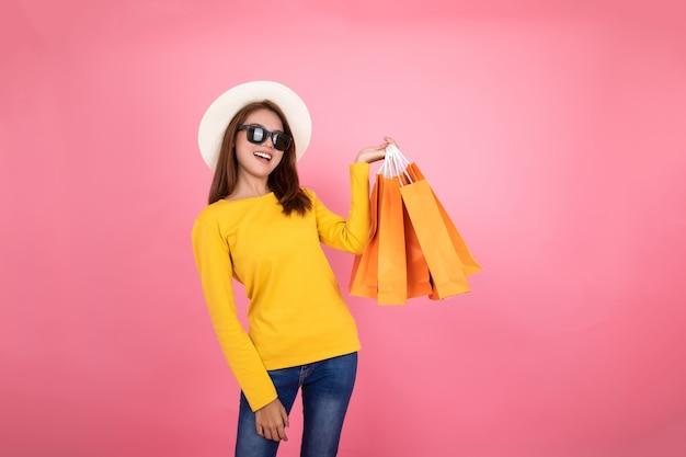 Borse arancio d'acquisto della tenuta graziosa asiatica della ragazza che distolgono lo sguardo sul fondo rosa, concetto variopinto di acquisto.