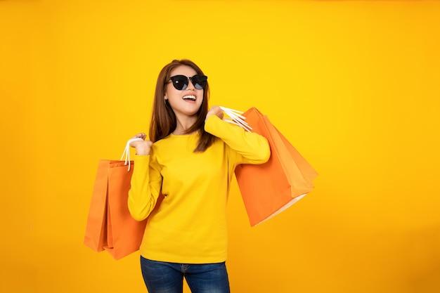 Borse arancio d'acquisto della tenuta graziosa felice asiatica della ragazza che distolgono lo sguardo sul fondo giallo, concetto variopinto di acquisto.