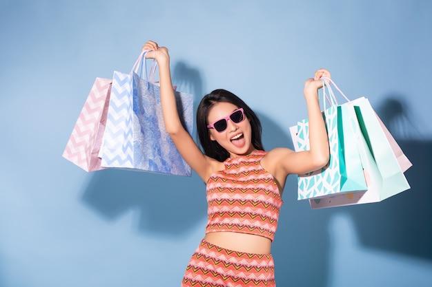 Borse della spesa e occhiali da sole della tenuta di estate della ragazza graziosa felice asiatica che osservano via