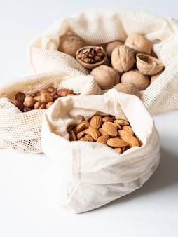 Borse riutilizzabili ecologiche in tessuto per lo stoccaggio o lo shopping con vari tipi di noci su sfondo bianco.