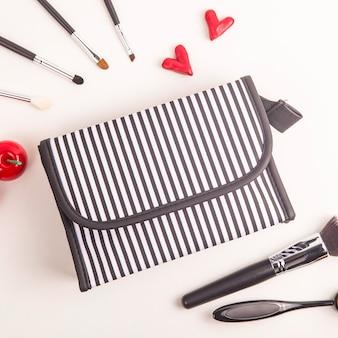 Borsello cosmetico in bianco e nero tra pennelli per il trucco e oggetti rosso acceso